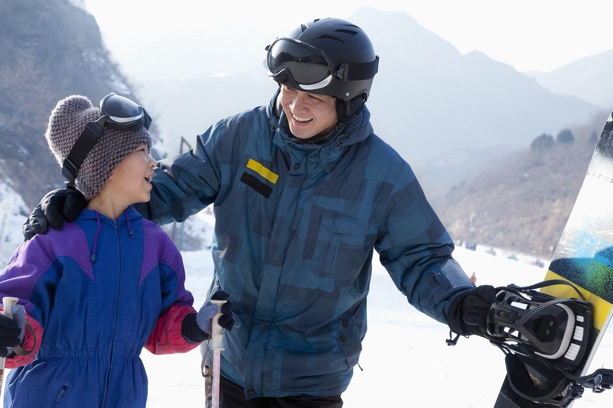 guy teaching kid how to ski