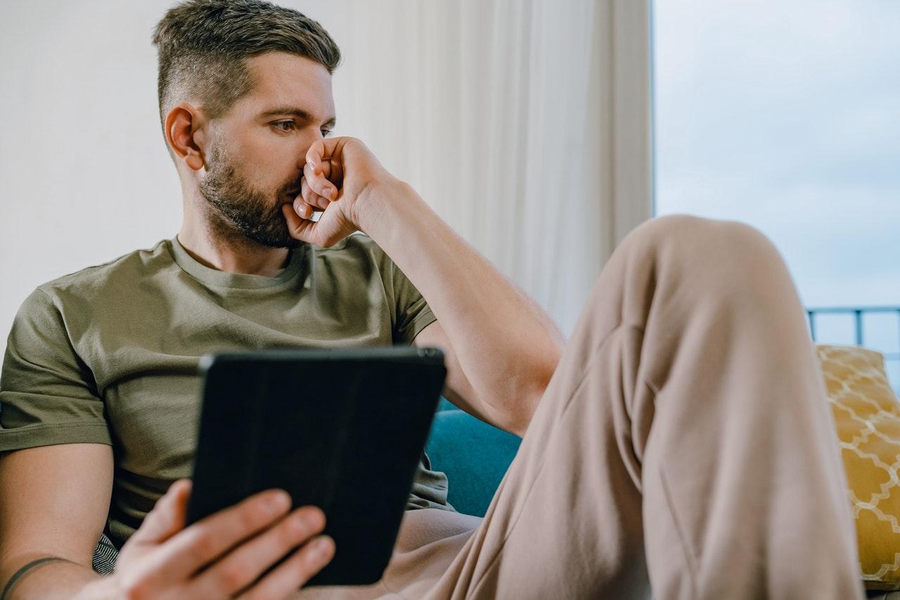 sad man holding a tablet