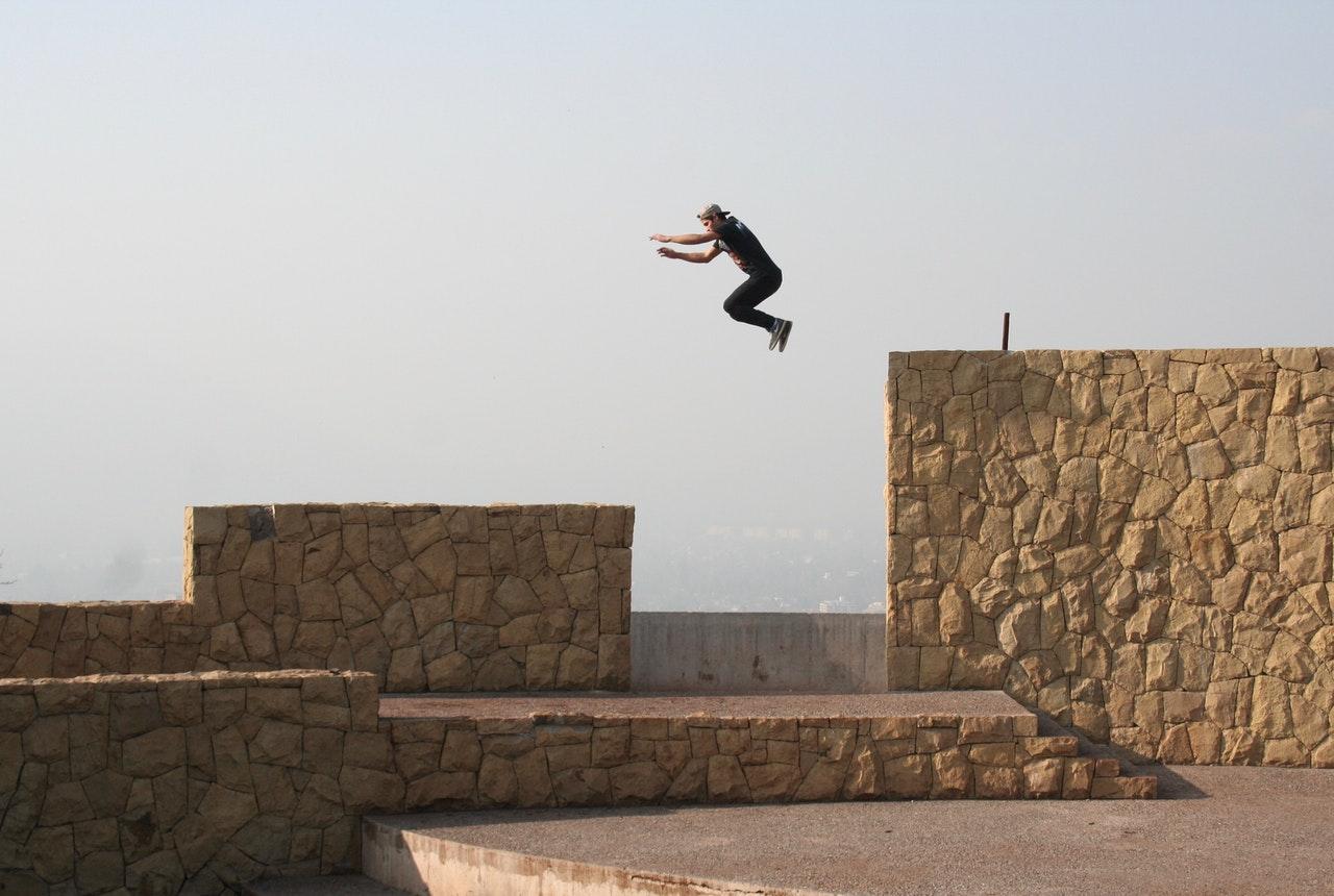 man jumping gap performing parkour